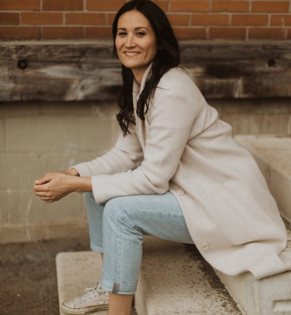 Emily Cassolato, Guelph realtor, sits on concrete stairs outdoors smiling into the camera.